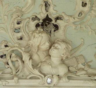 Stuckrelief einer Amorette, die sich im Löwenfell zu Amor beugt, im Bilderkabinett im Neuen Schloss Tettnang