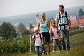 Wandernde Familie im Hopfengarten